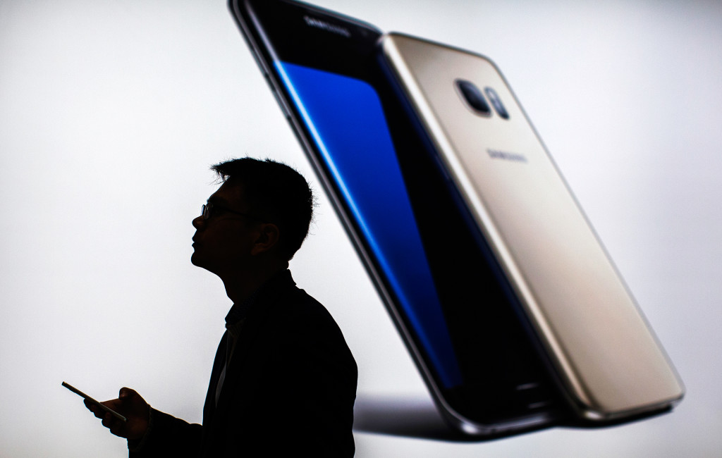 A man holds his smart phone at the Mobile World Congress wireless show, in Barcelona, Spain, Monday, Feb. 22, 2016.  (AP Photo/Emilio Morenatti)